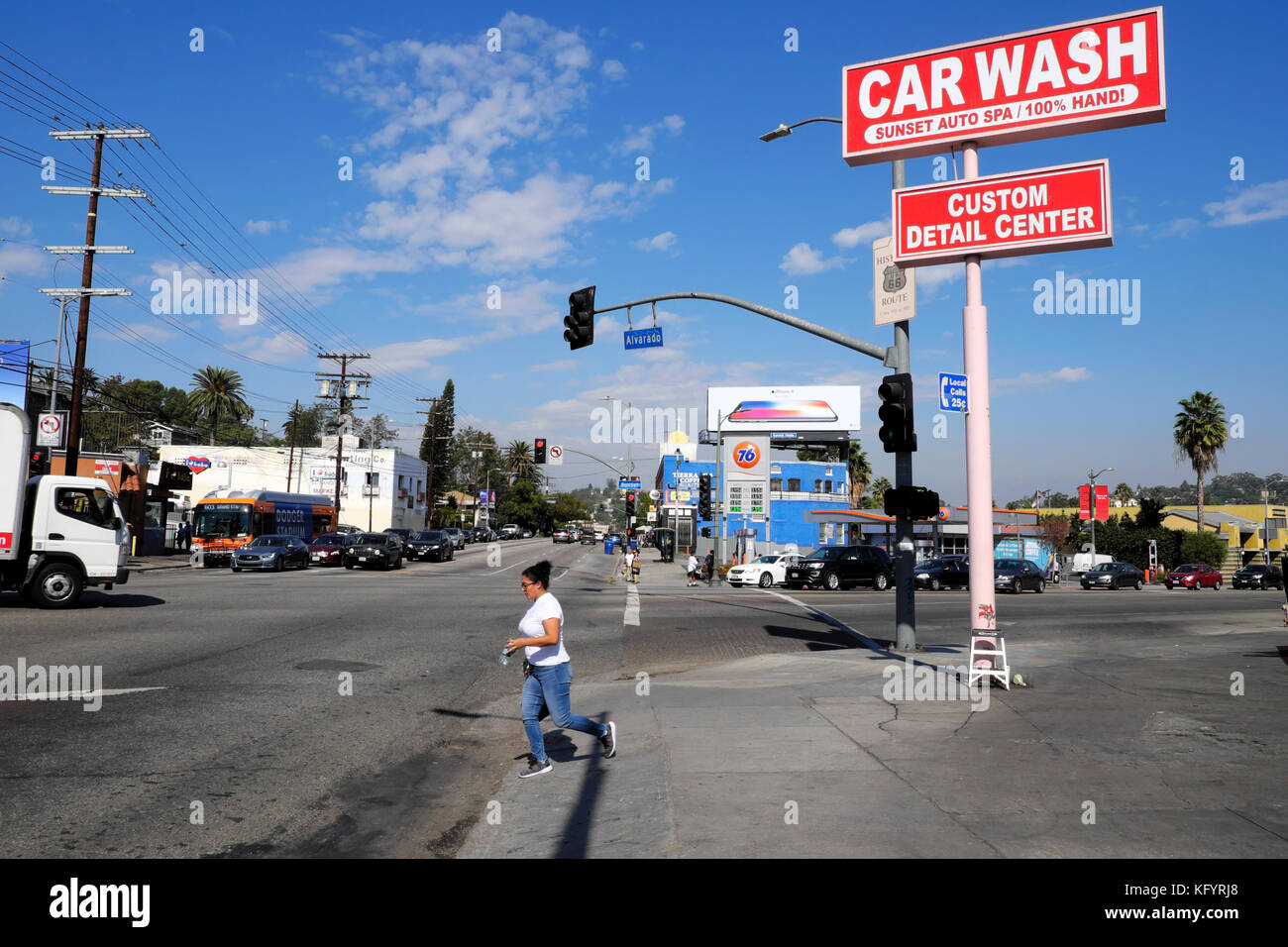 Woman crossing the road by Car Wash sign on the corner of  Sunset Boulevard and North Alvarado Street in Echo Park - Stock Image