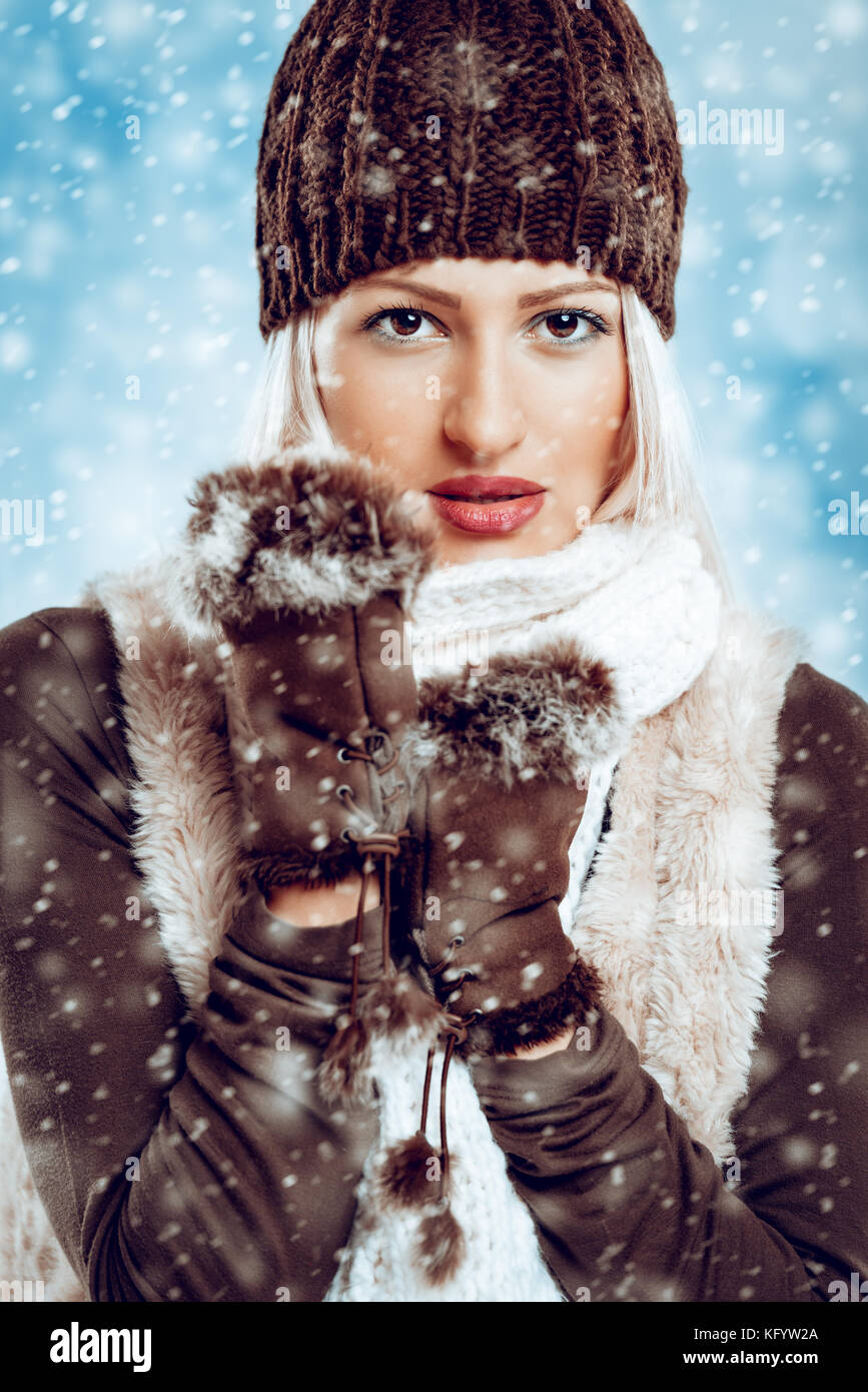Beautiful young girl in winter clothes with a wool cap and fur gloves, sticks to the wool scarf in which is tucking - Stock Image