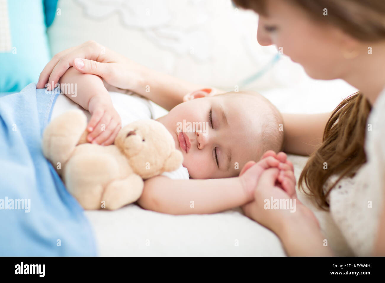 Motherhood. Parenthood. Young mother looking at her baby sleeping in bed - Stock Image