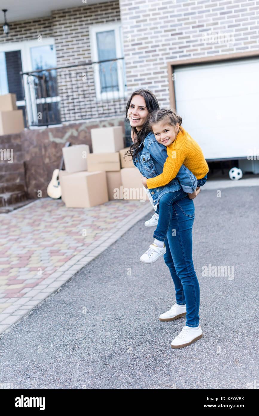 daughter piggyback riding mother - Stock Image