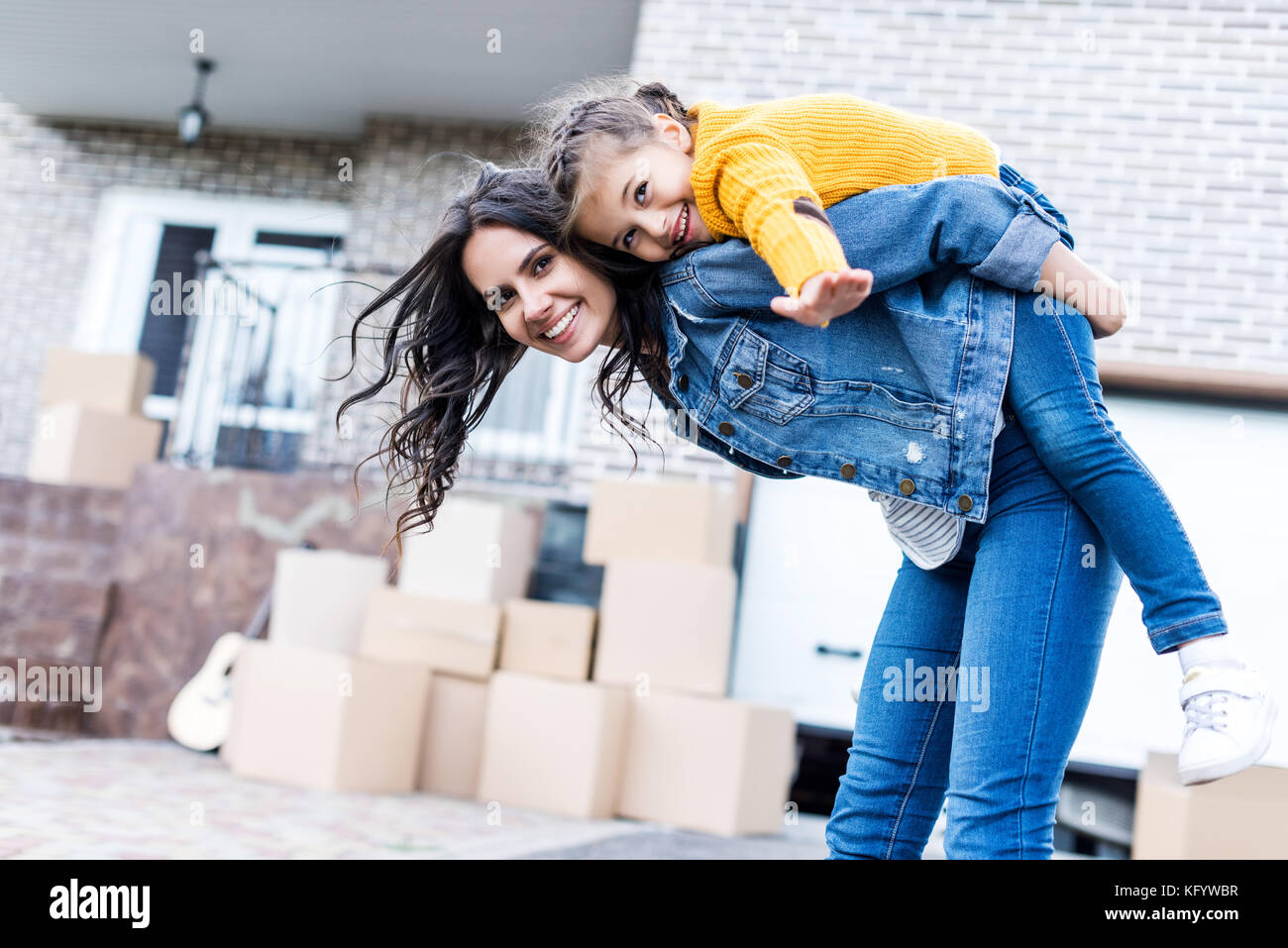 daughter piggyback riding mother - Stock Image