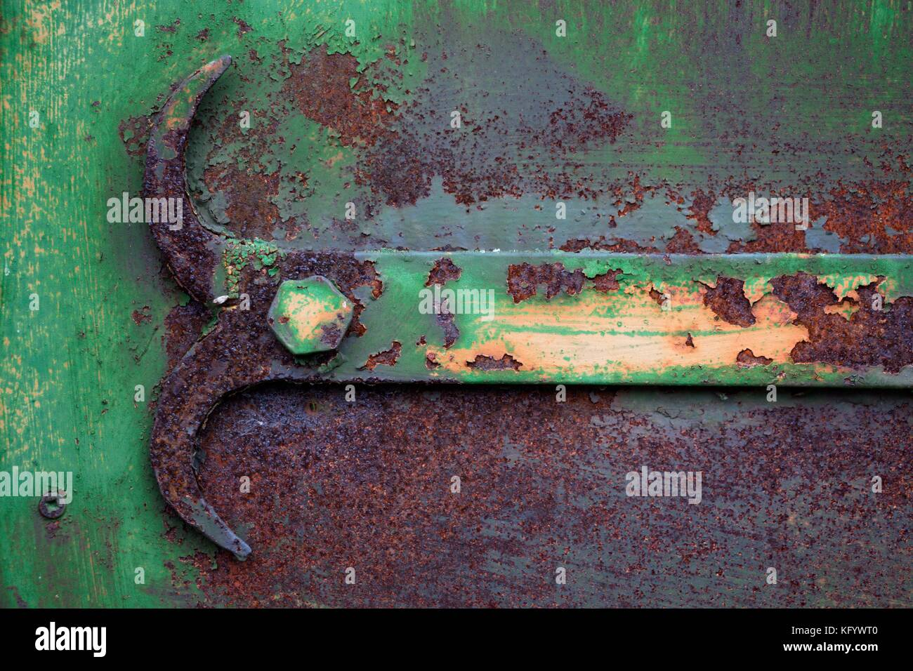 Part of the mechanism for opening the door, painted in a green tint and heavily rusted, spoiled by time. The mechanism - Stock Image