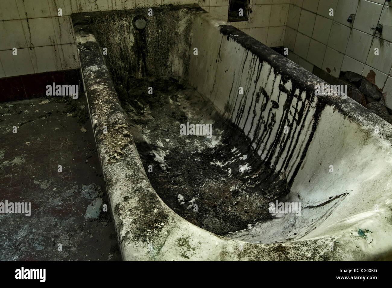 an old tub inside an abandoned psychiatric hospital, very dirt and encrusted - Stock Image