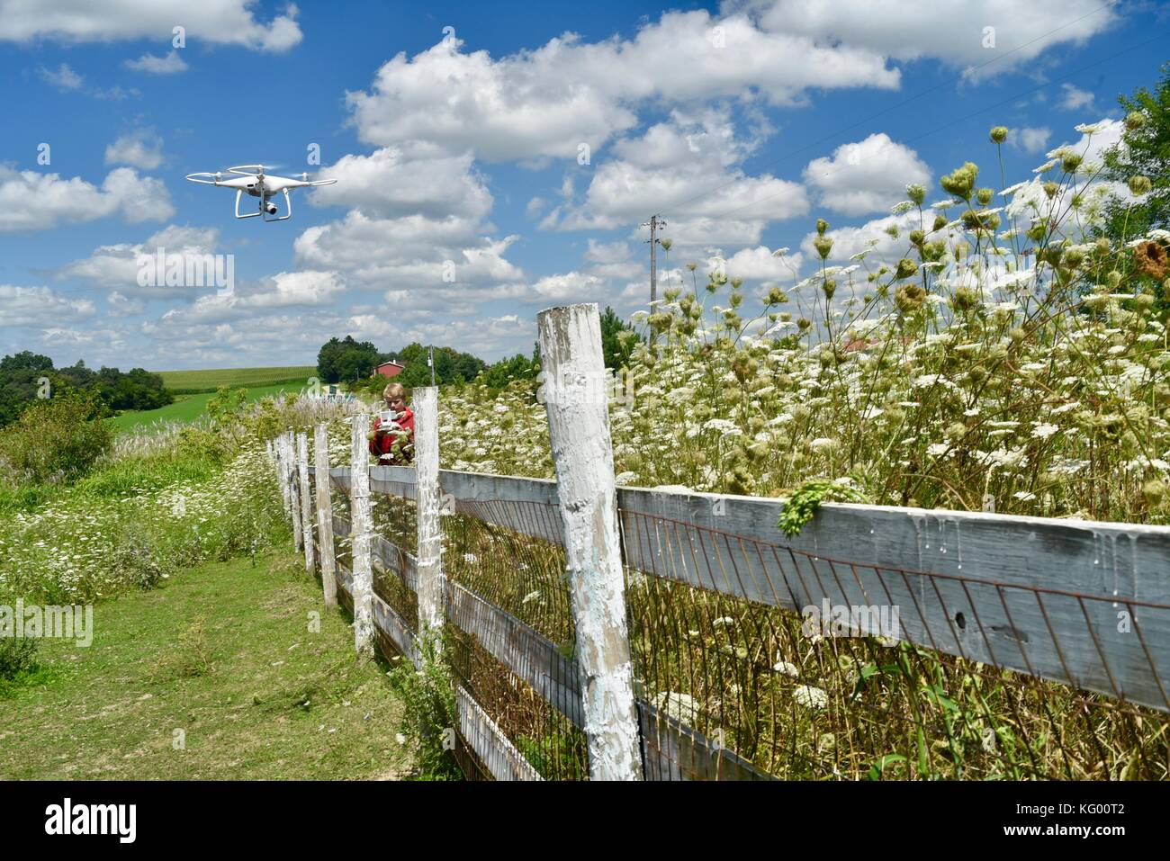 Teen boy flying DJI Phantom 4 Pro+ Drone to check fencing on rural farm in USA. - Stock Image