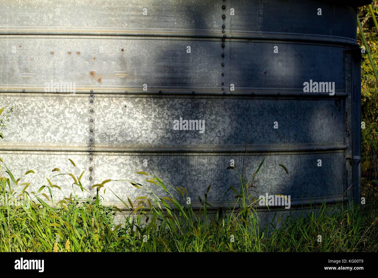 Galvanized bin in the green grass - Stock Image