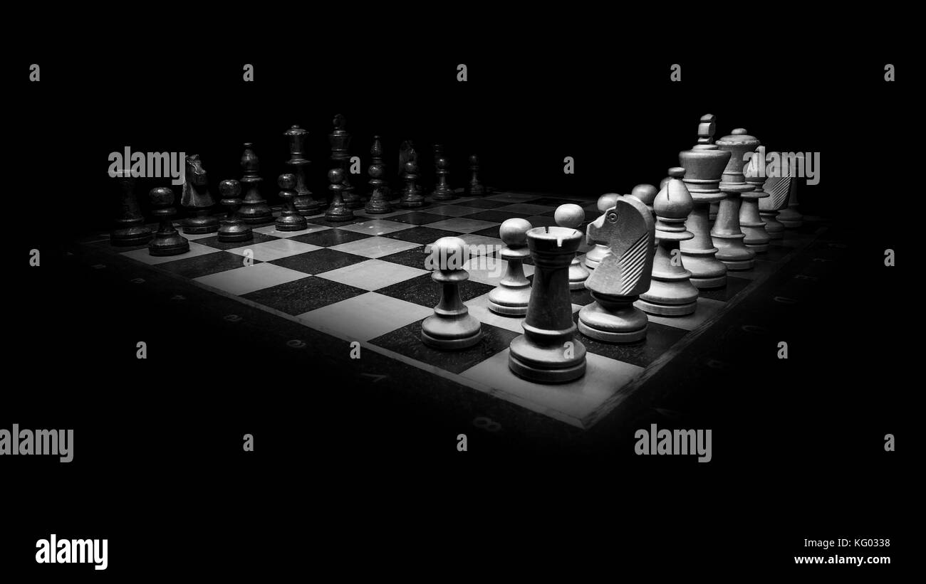 Two Chess teams on a Chess board in beginning position in a dark room. - Stock Photo