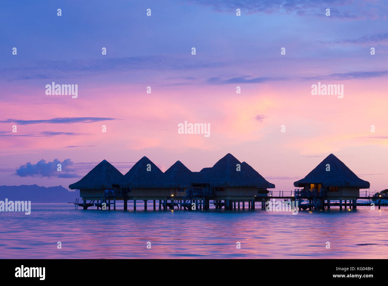 A pink sunset is reflected in the water below elevated bungalows in the Intercontinental Le Moana resort in Bora Stock Photo