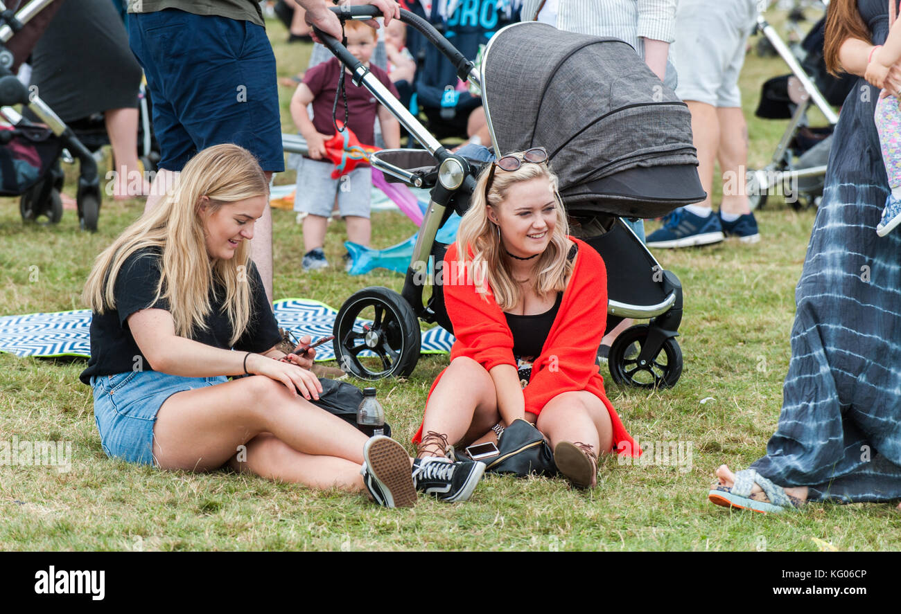 Two young women sitting on the ground at Coventry Godiva Music Festival, Coventry, West Midlands, UK. - Stock Image
