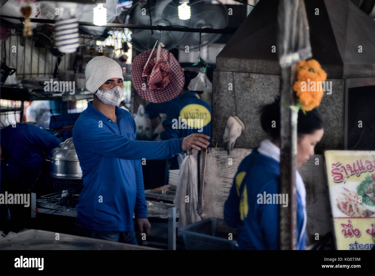 Anti pollution face mask. Thailand BBQ cook wearing smog and facemask protection. - Stock Image