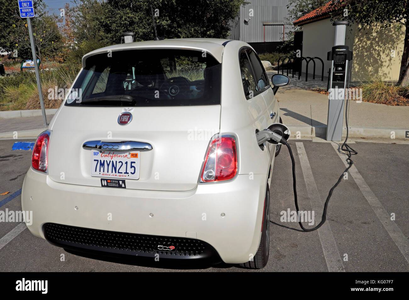 Fuel efficient small Fiat electric car recharging battery at charging station parking lot in East Los Angeles, California - Stock Image