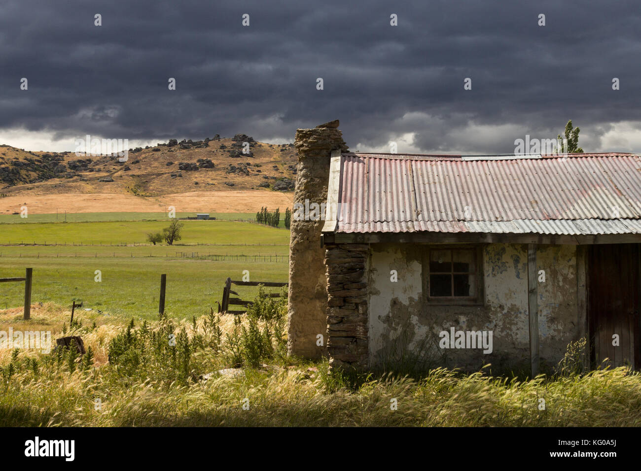 An abandoned cottage beneath gathering storm clouds in the Catlins, New Zealand - Stock Image