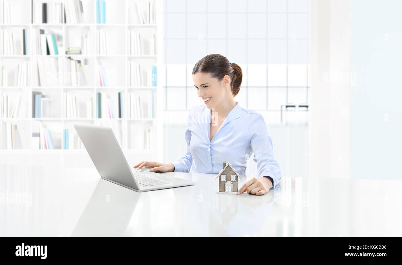 home concept smiling woman use the computer and showing house model, real estate and design - Stock Image
