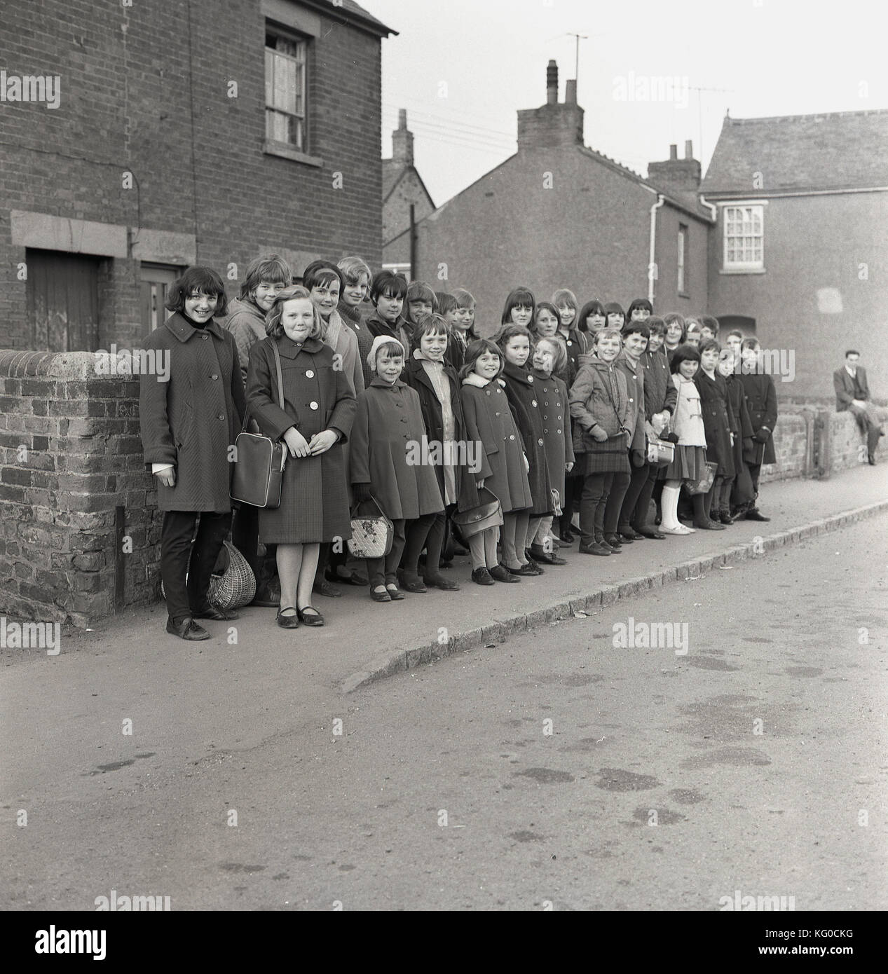 1950s, historical, post-ww2 Britain and a group of excited children of different ages wait stand together on a pavement Stock Photo
