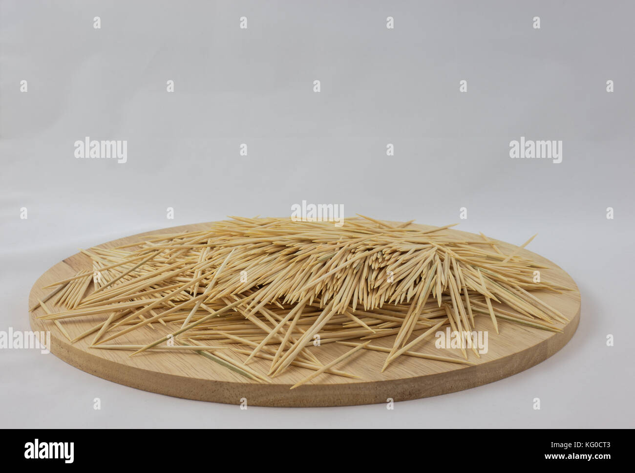 Toothpicks piled on a round wooden plate - Stock Image