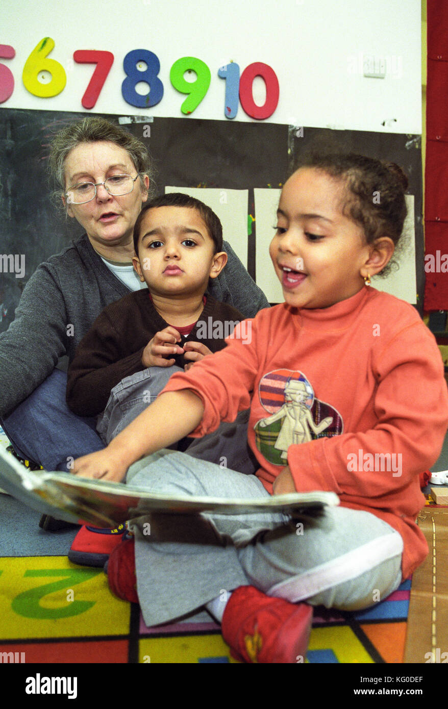 Teacher reading to children at a nursery school - Stock Image