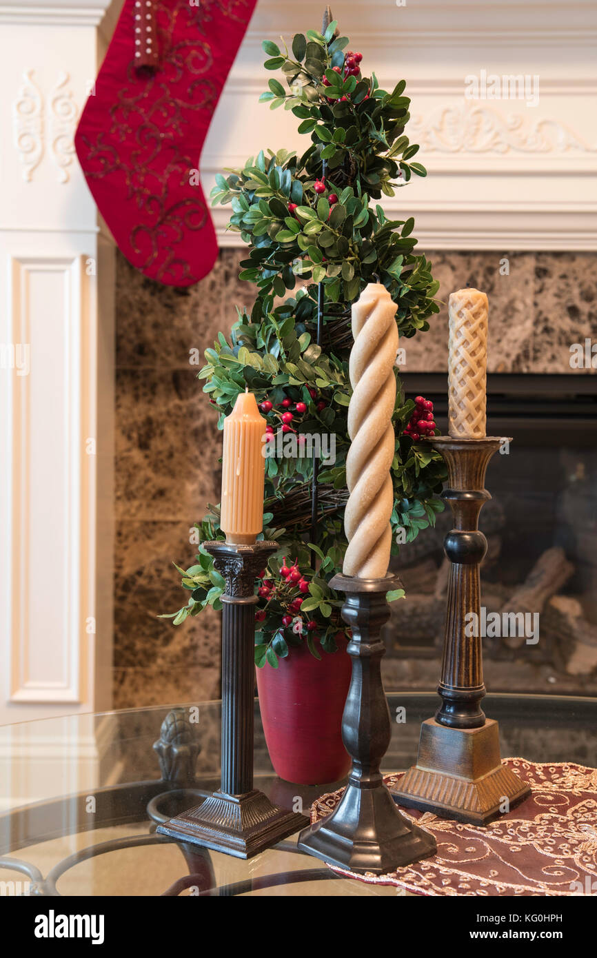 Living room decorated for Christmas with candlesticks, and a stocking hung at the fireplace mantle Stock Photo