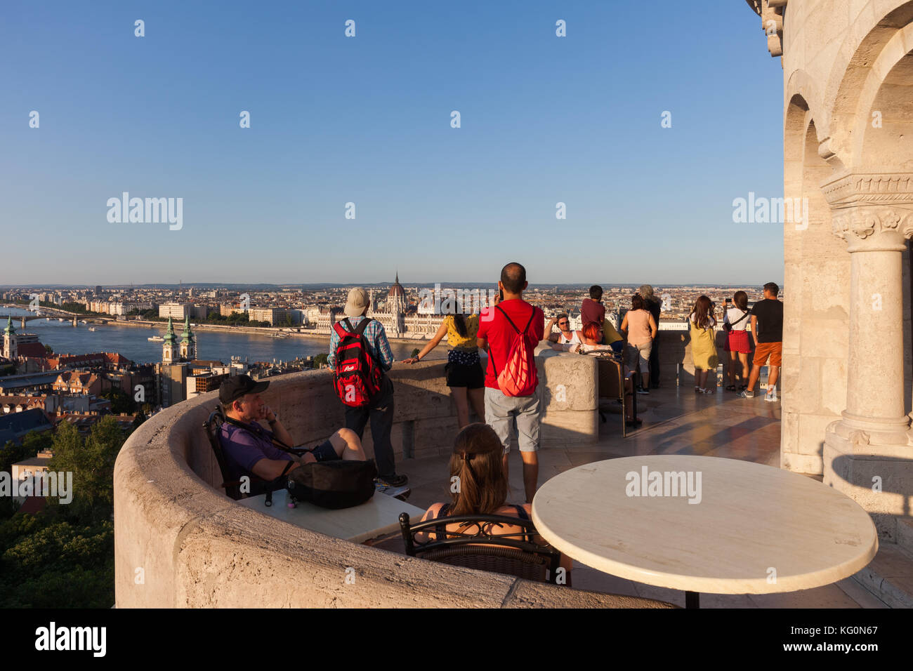 People, group of tourists on Fisherman's Bastion viewpoint terrace at sunset overlooking city of Budapest in - Stock Image