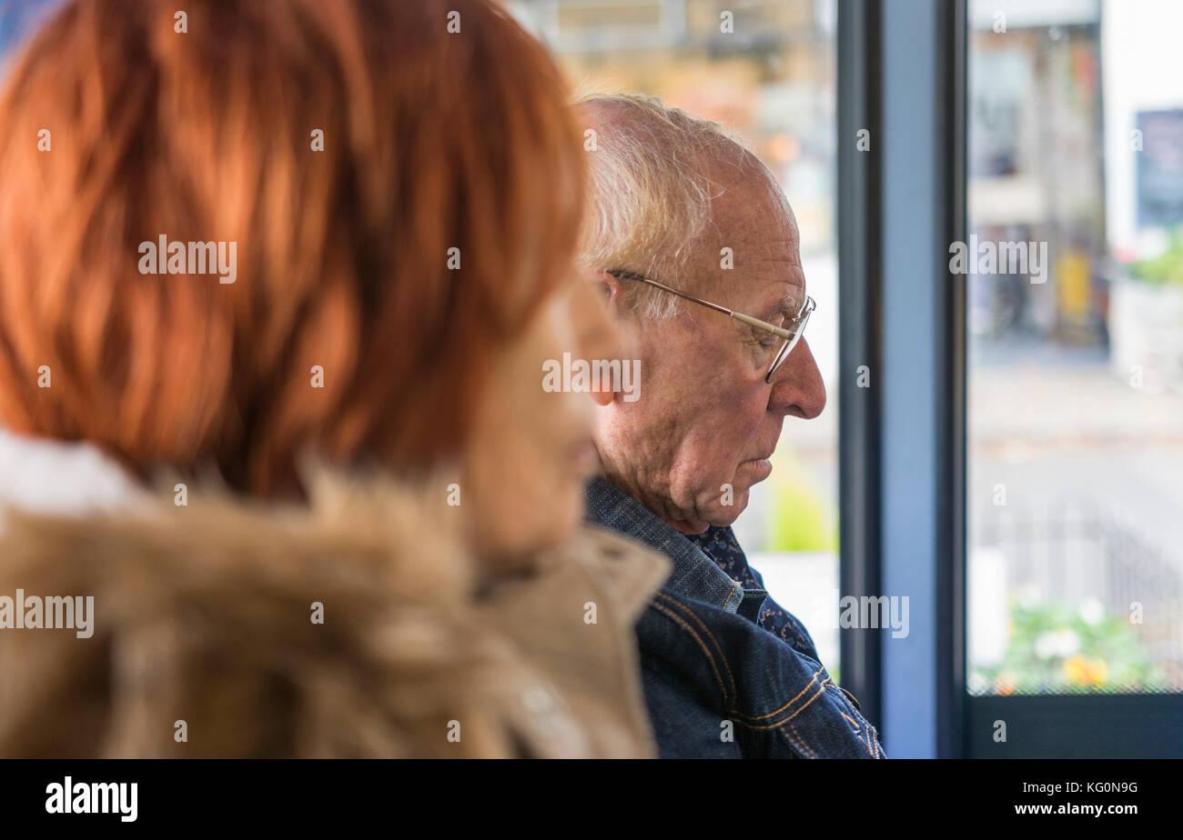 Elderly couple sitting on a bus sleeping. - Stock Image