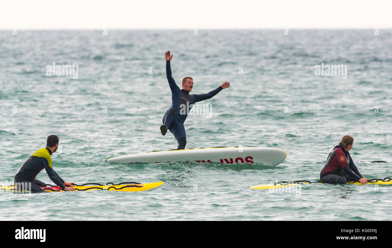 Man falling off a paddle board into the sea. - Stock Image