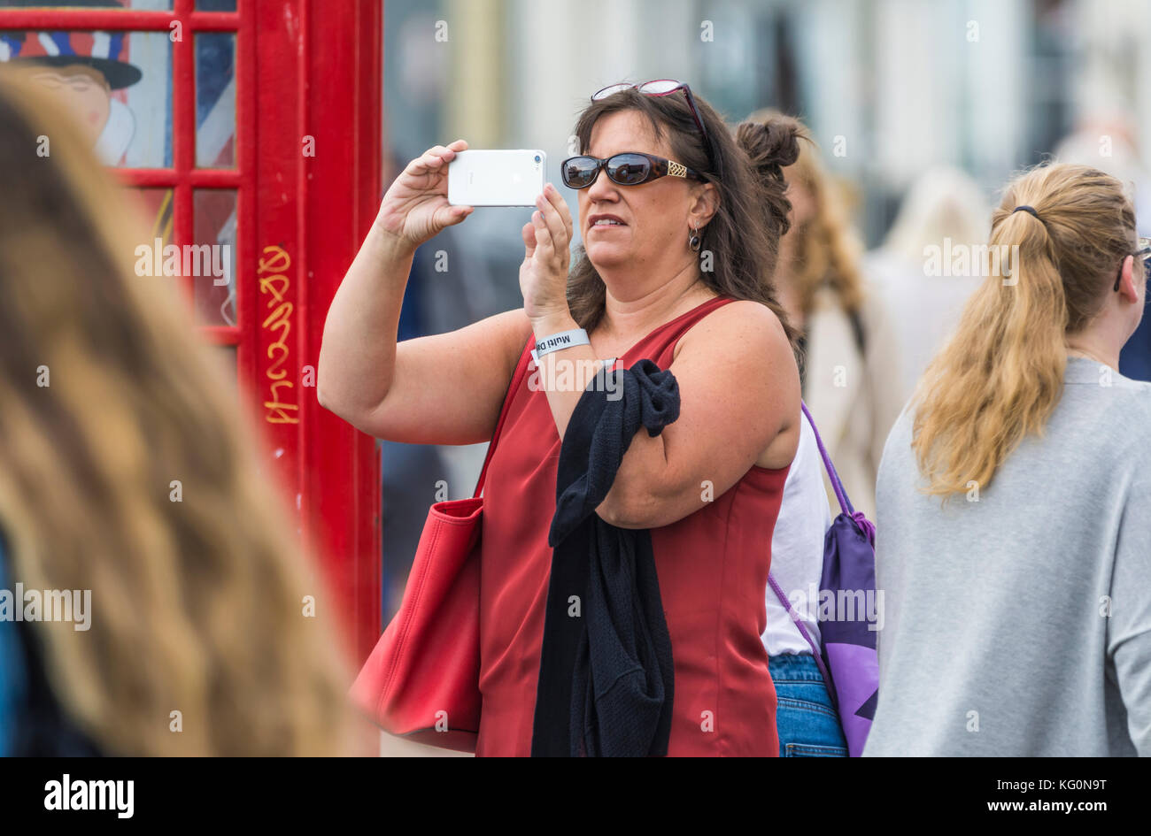 White female tourist taking photos using a smartphone camera in a crowded area in the UK. - Stock Image