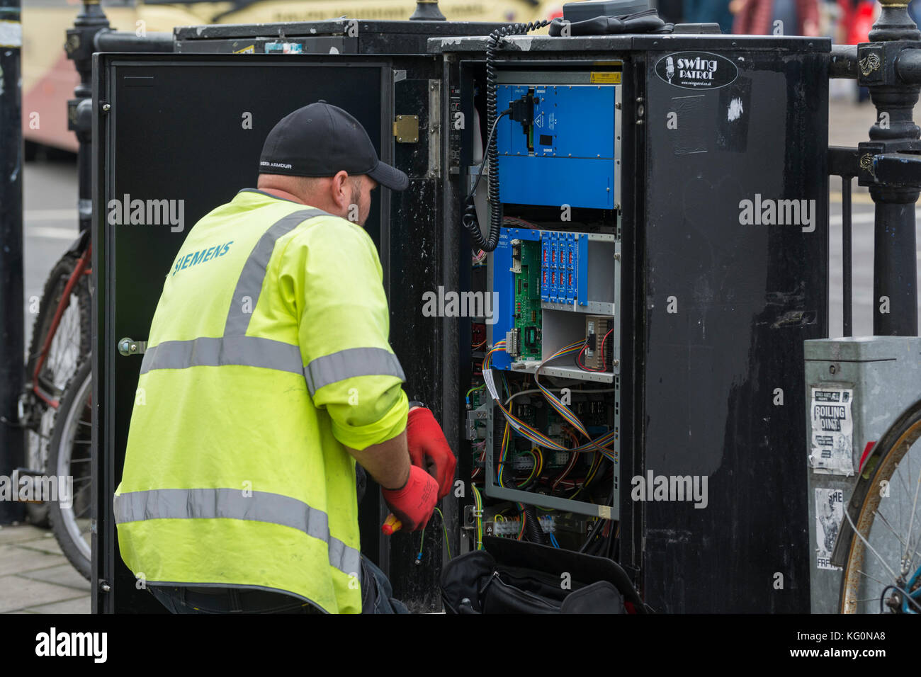 Siemens employee performing maintenance on a communications cabinet in the street in the UK. - Stock Image
