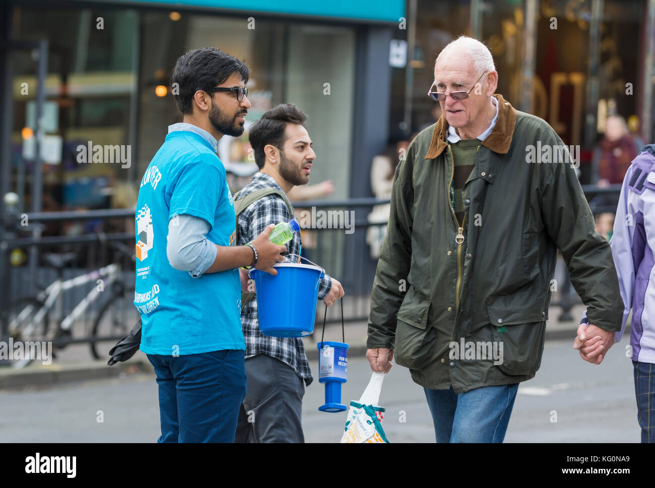 Man walking past people collecting for charity. NOTE: This man was NOT ignoring them. This is a concept image just - Stock Image