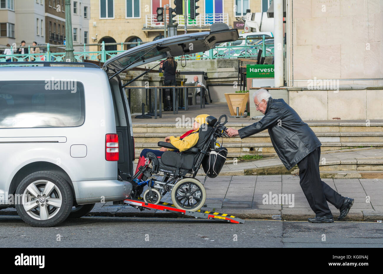 Man pushing disabled child in a wheelchair up a ramp into a car. - Stock Image