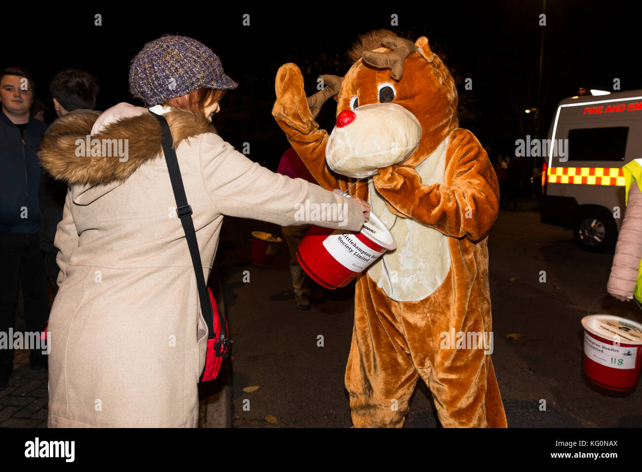 A woman making a donation by putting money in charity collection box at a fancy dress procession in the UK. - Stock Image