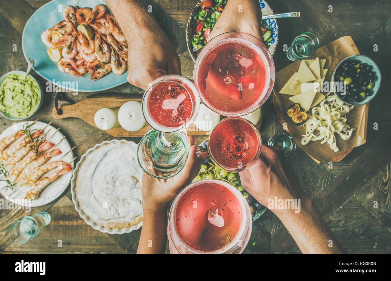 Flat-lay of friends hands eating and drinking together, horizontal composition - Stock Image