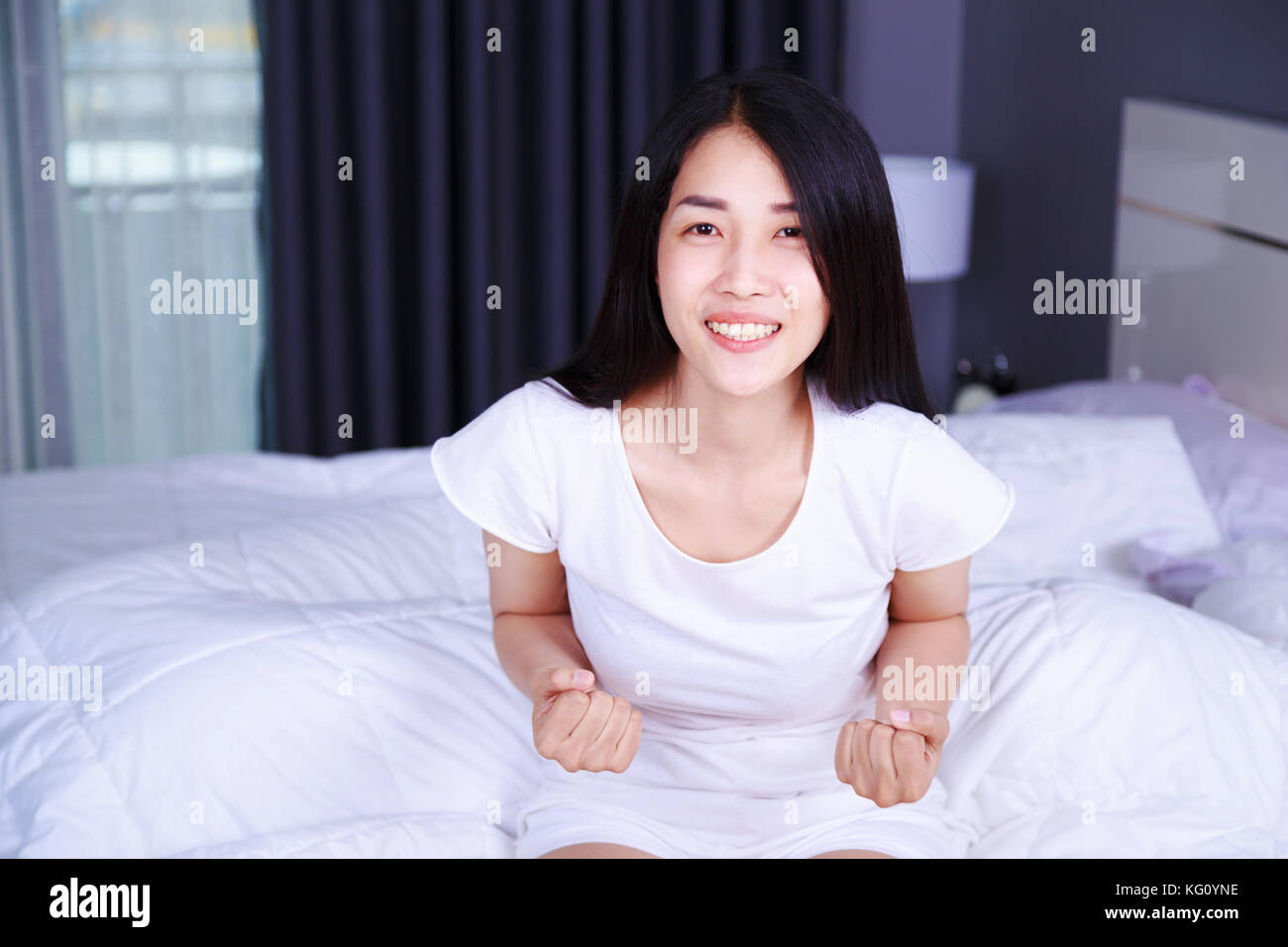 happy woman on bed in the bedroom - Stock Image