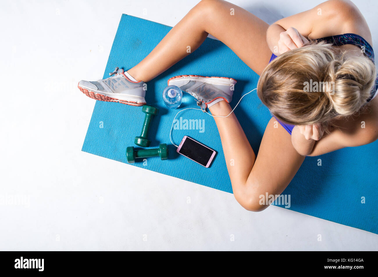 Female fitness model resting after an intense workout and taking some a selfie in the mirror of the gym. - Stock Image