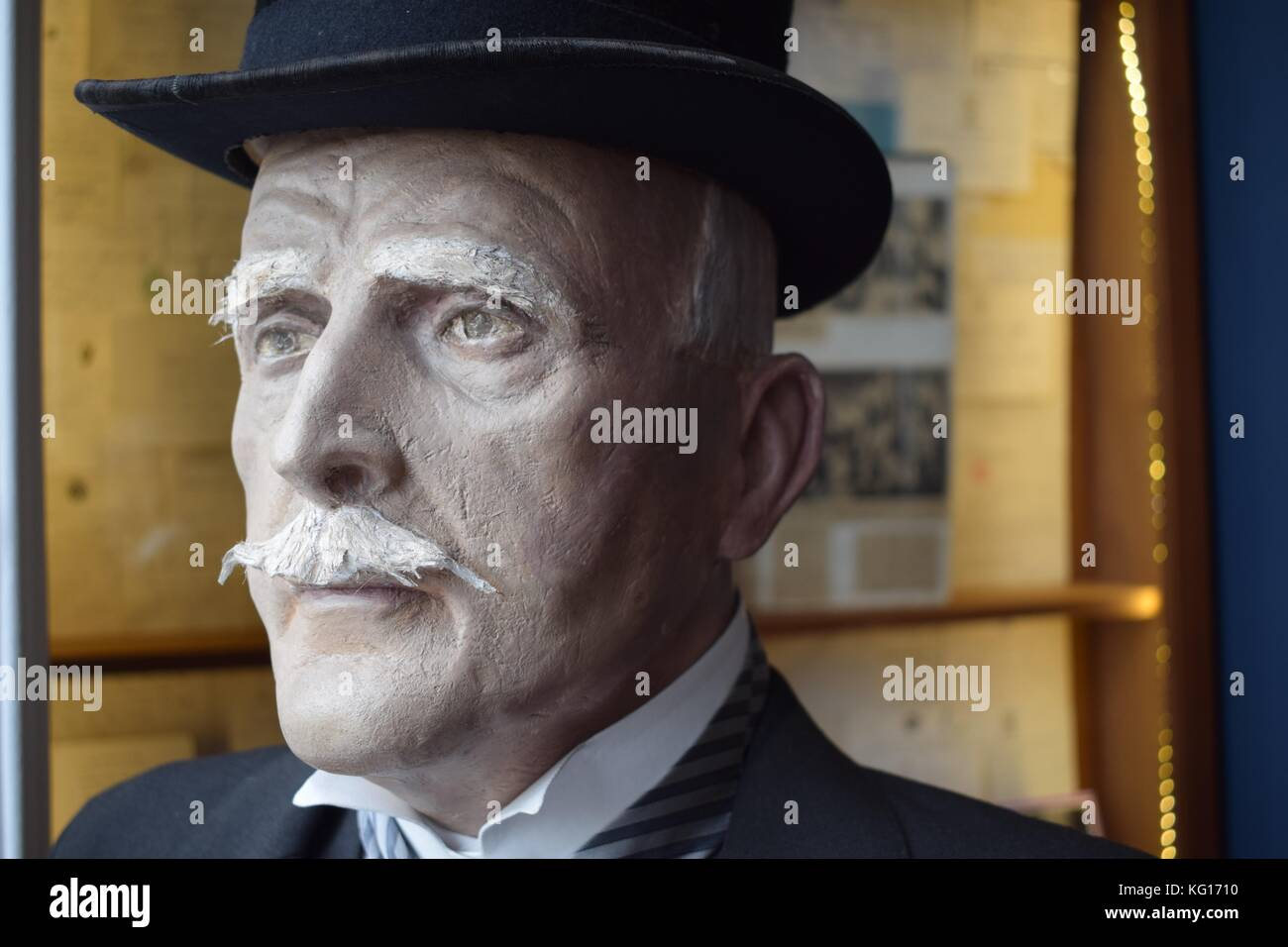 Statue of an old gentleman looking out of a window. - Stock Image
