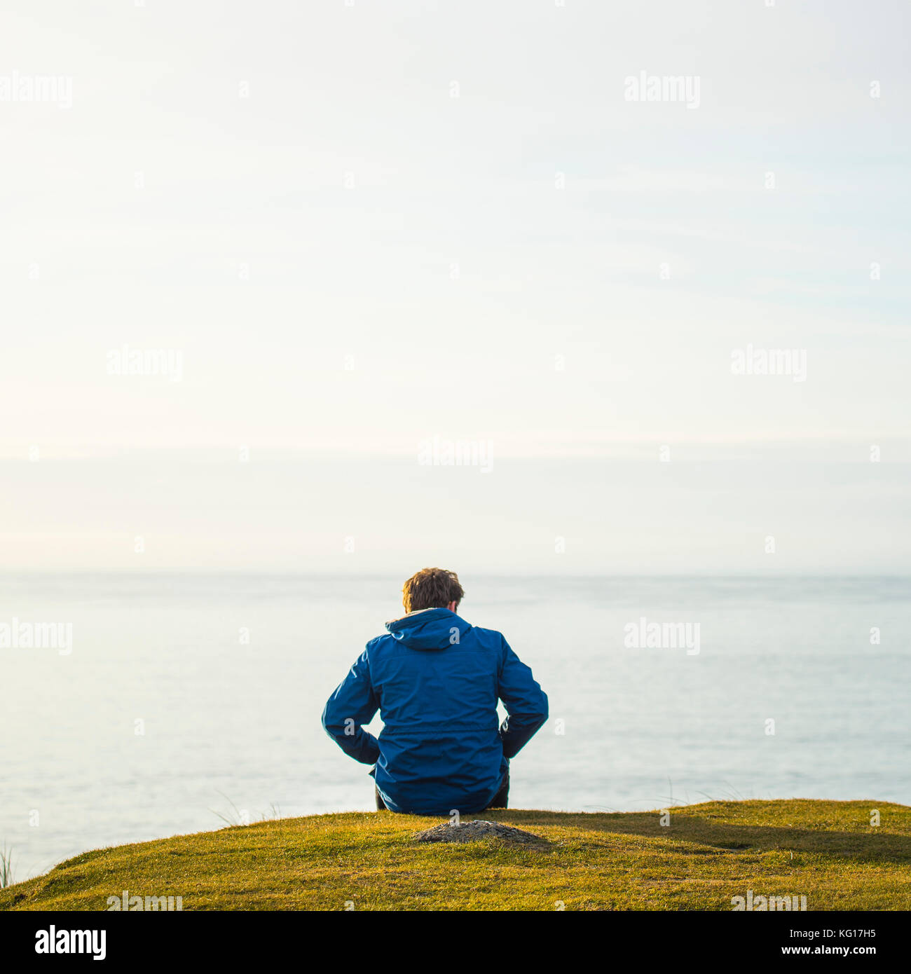 Lone person looking out to sea - Stock Image