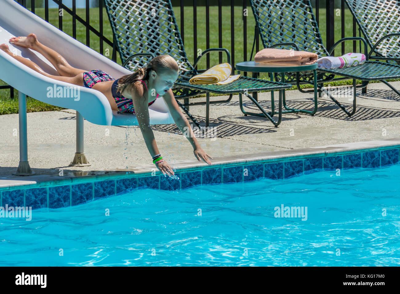 Young Girl Sliding Down A Pool Slide   Stock Image