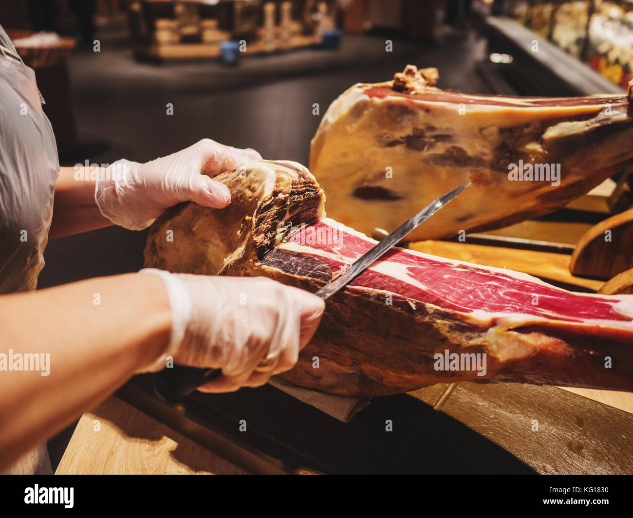Hands of a woman in gloves in the market or store cut a slice of traditionally spanish jamon de bellota. Meat close - Stock Image