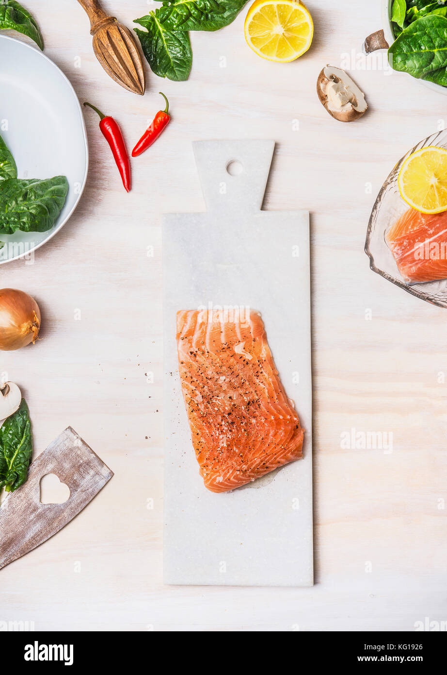 Raw Salmon fillets on white cutting board with healthy ingredients ...