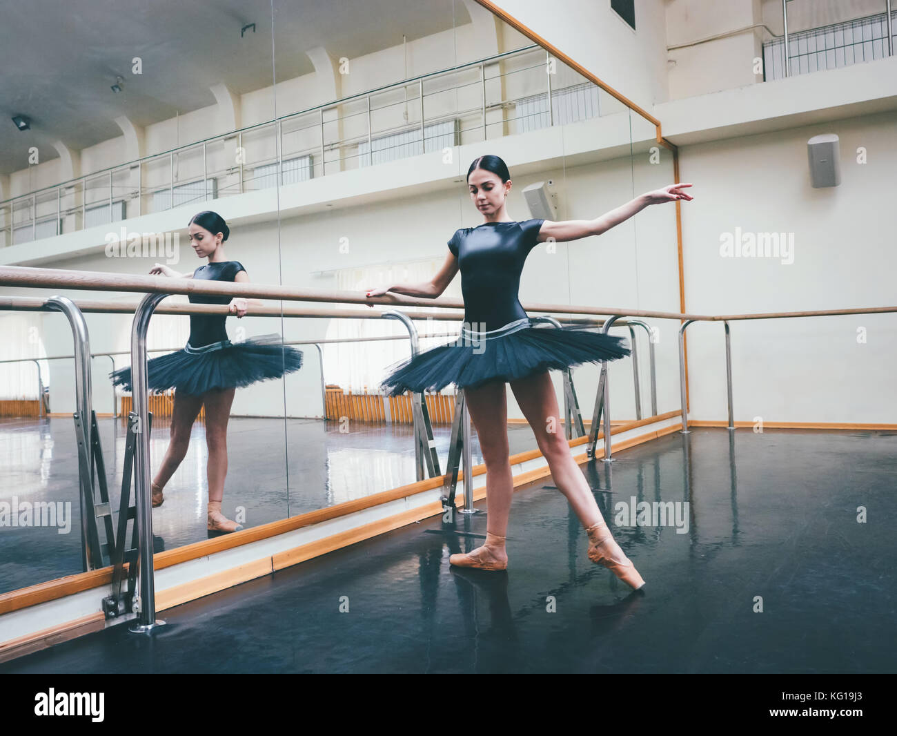 Ballerina in black tutu and pointe stretches on barre in ballet gym. Woman standing near bar and mirror, preparing Stock Photo