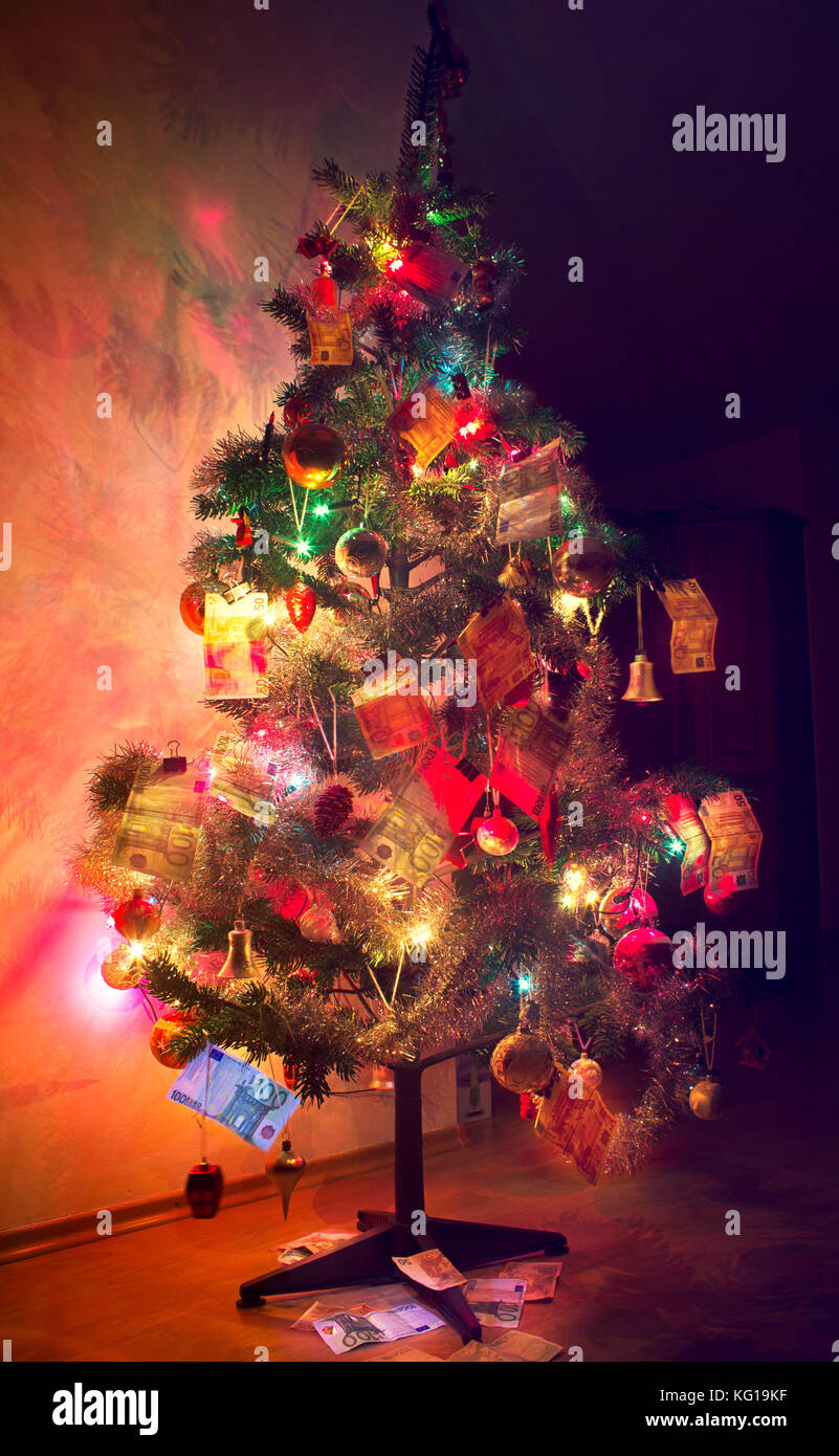 A vertical image of Christmas tree decorated with money (EUROS) - Stock Image