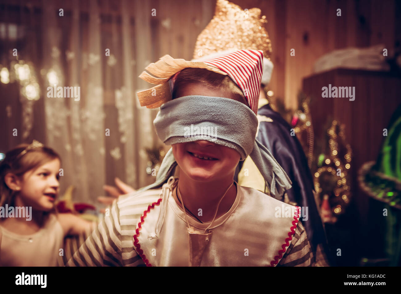 Happy child in carnival costume of Pinocchio during Christmas holidays celebration - Stock Image
