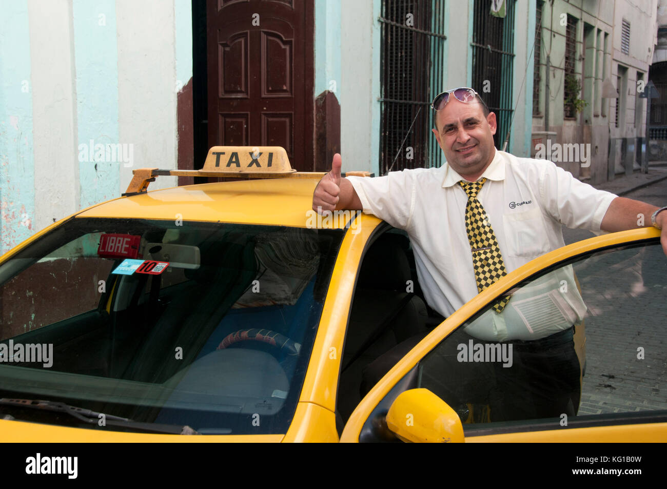 Official Tourist Taxi & Taxi Driver in Uniform in the Back Streets of Old Havana, Habana Vieja, Cuba - Stock Image