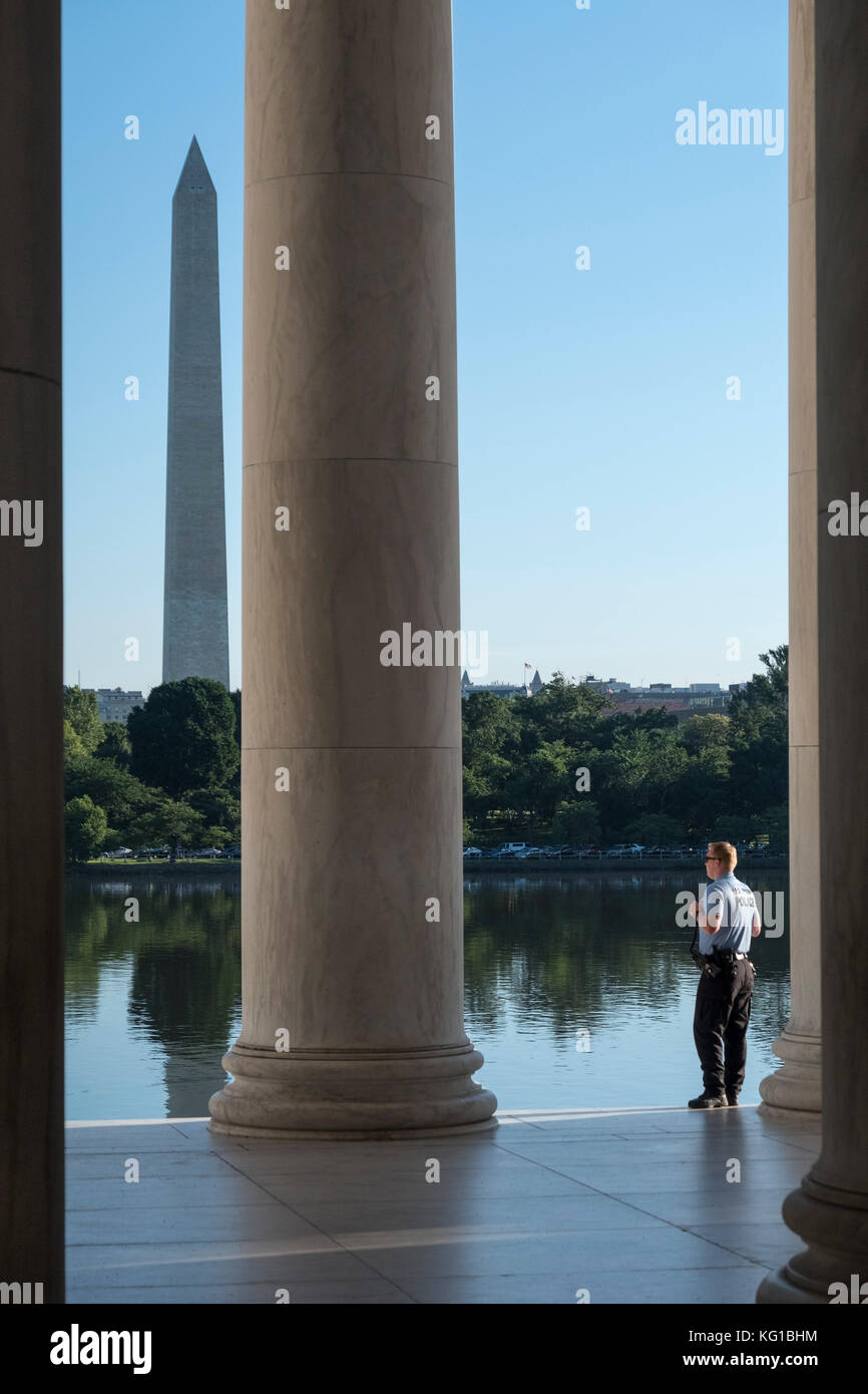 US Park Police Officer standing guard at the Jefferson Memorial with the Washington Monument behind, National Mall, - Stock Image