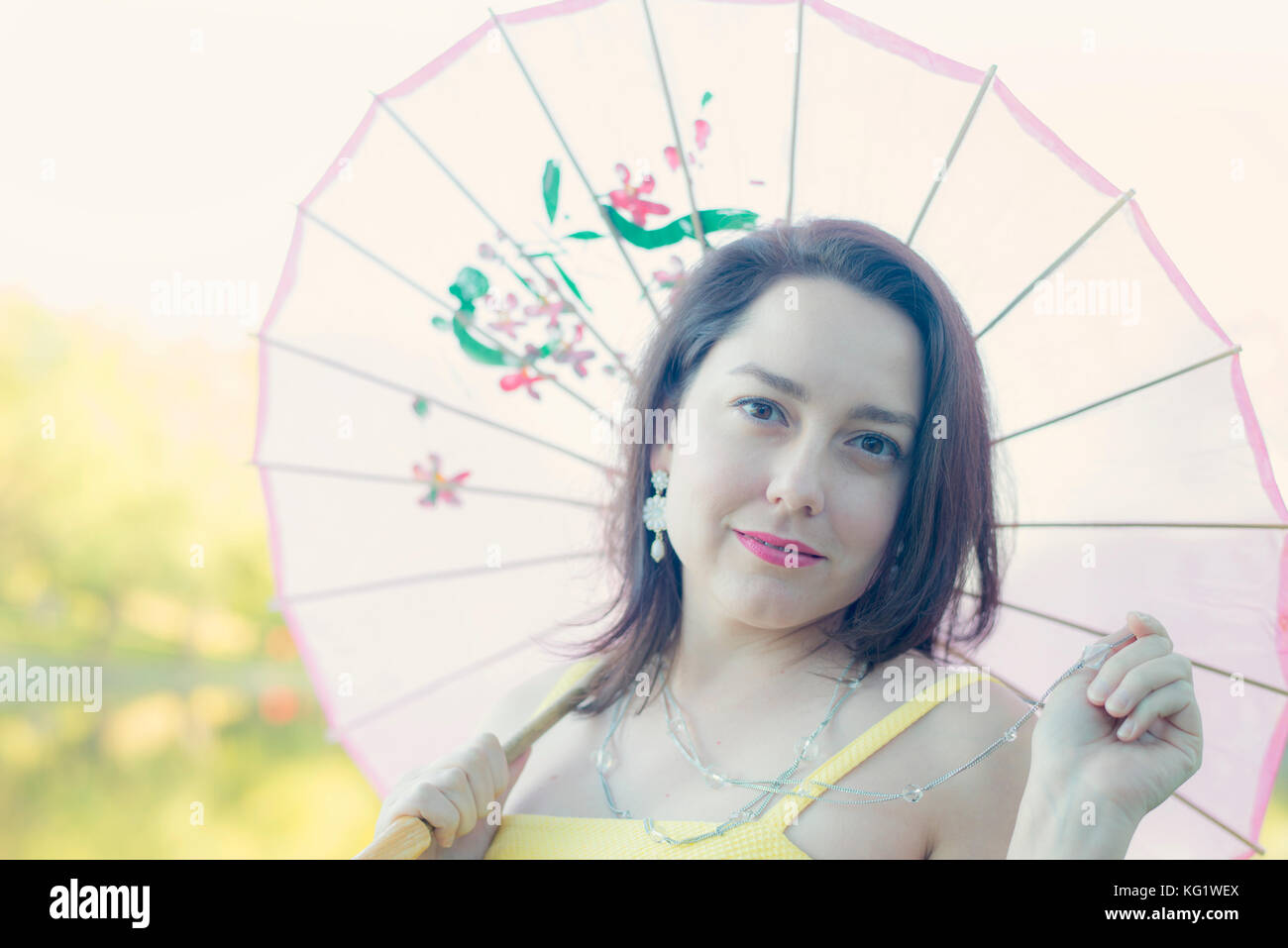 Woman with light shining through a parasol - Stock Image