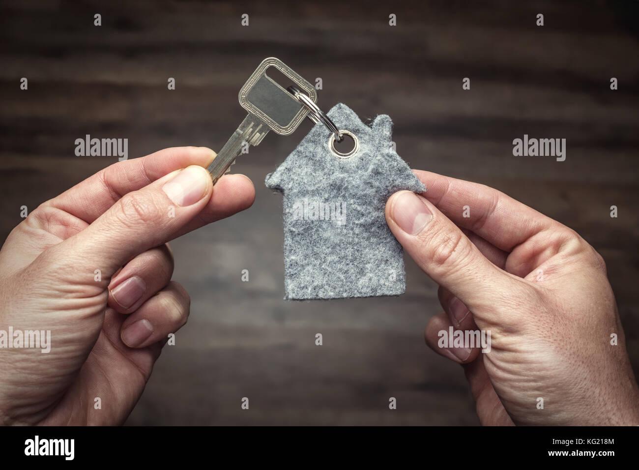 Latchkey in between two hands - Stock Image
