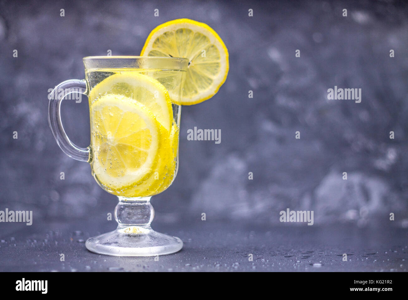 Homemade lemonade in a glass with a handle on a gray concrete background. Water with slices of lemon on a dark background. - Stock Image