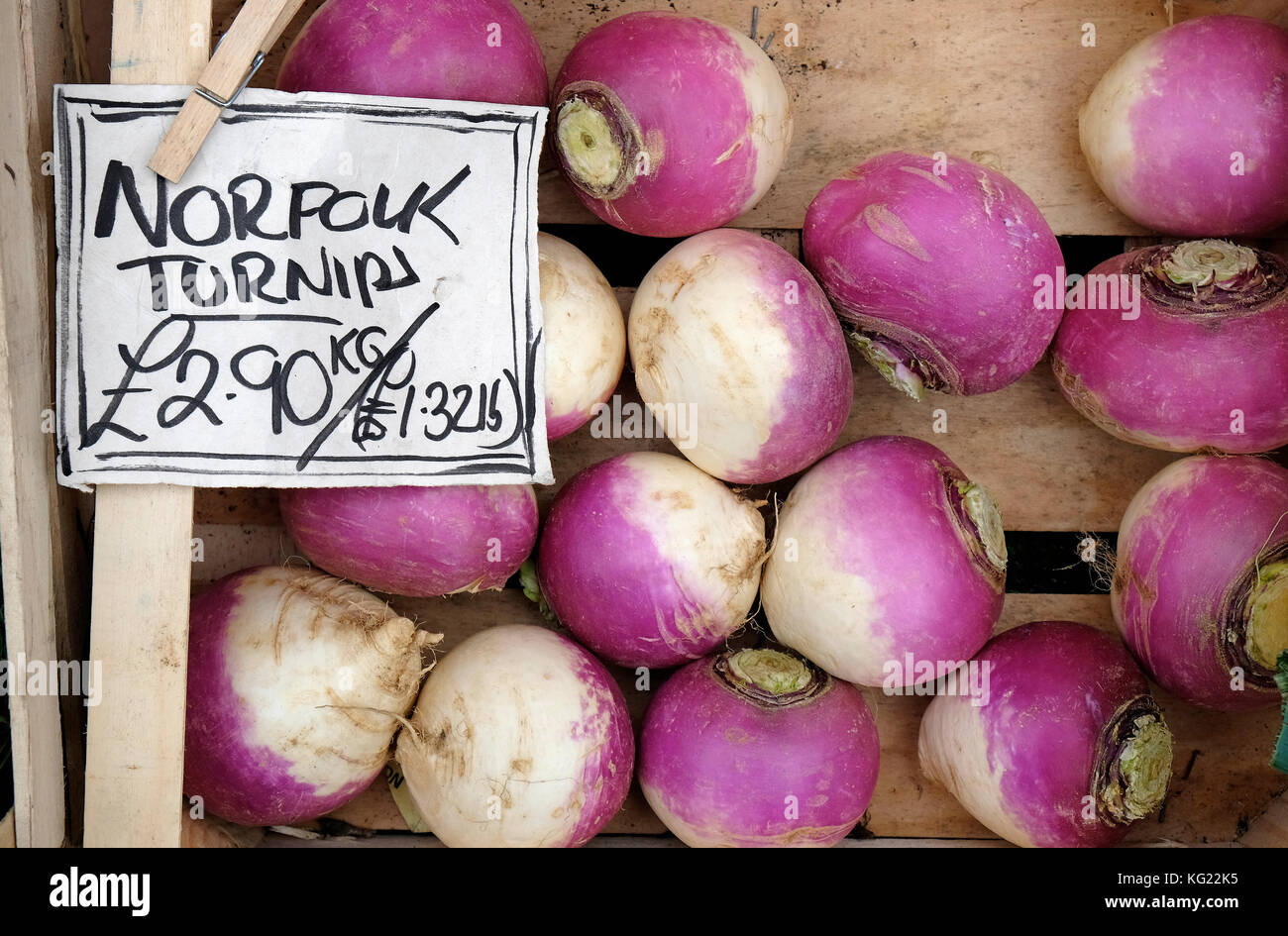 norfolk turnips in wooden tray outside greengrocers shop - Stock Image