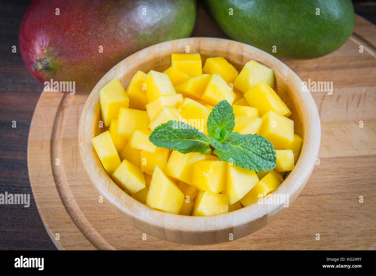 Tropical fruit mango in a plate on a wooden background, whole or sliced Stock Photo