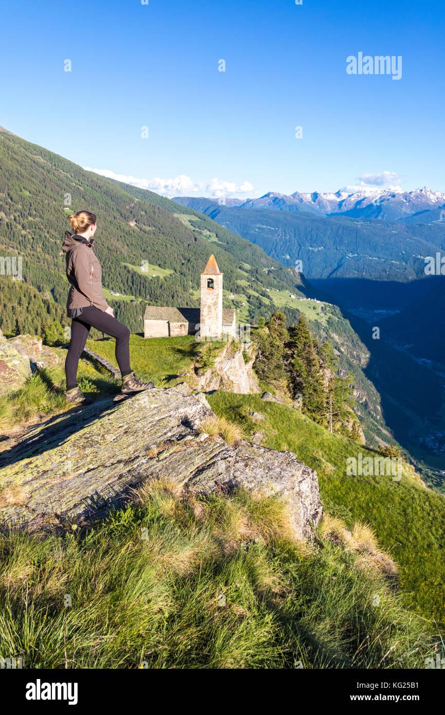 Woman looks at old church perched on mountains, San Romerio Alp, Brusio, Canton of Graubunden, Poschiavo Valley, - Stock Image
