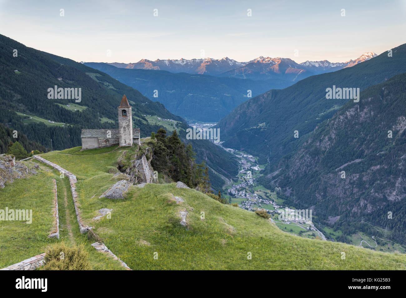 Ancient church at sunrise, San Romerio Alp, Brusio, Canton of Graubunden, Poschiavo Valley, Switzerland, Europe - Stock Image