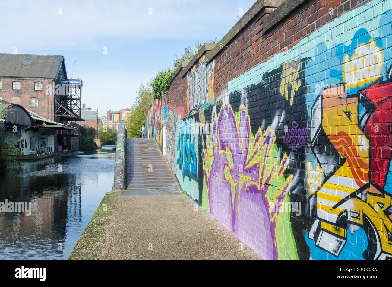 Colourful graffiti painted on brick walls beside the Digbeth Branch Canal towpath in Digbeth, Birmingham, UK - Stock Image