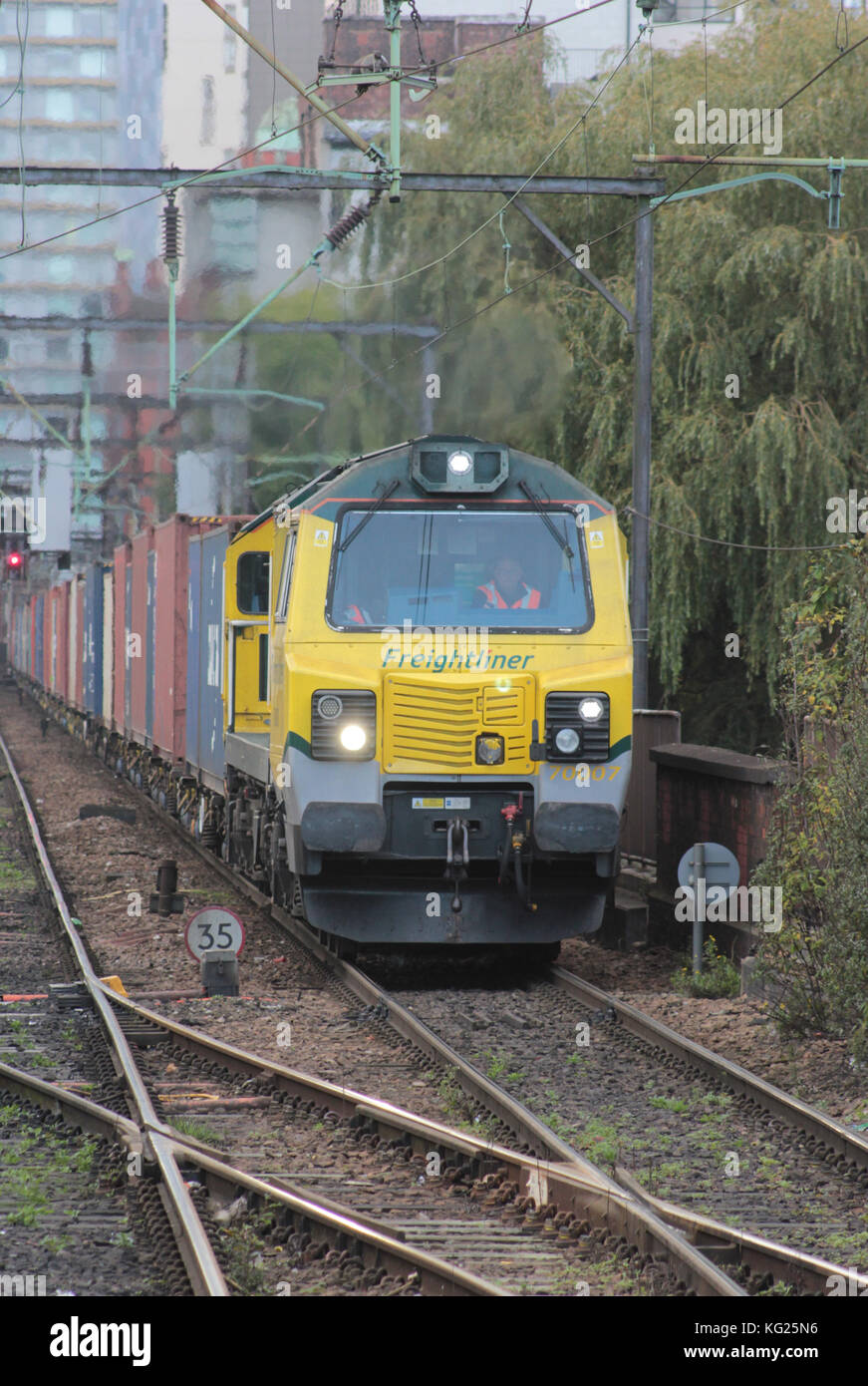A Freightliner container train approaches Manchester Piccadilly train station hauled by diesel locomotive no 70007. - Stock Image